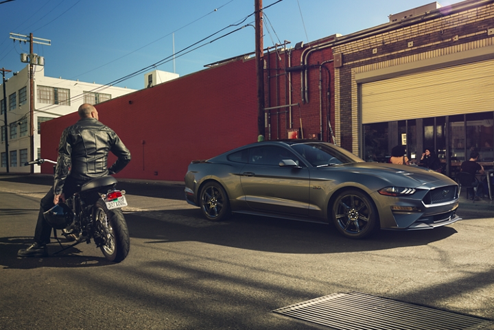 A man on a motorcycle looking at a 2020 Ford Mustang parked on city street