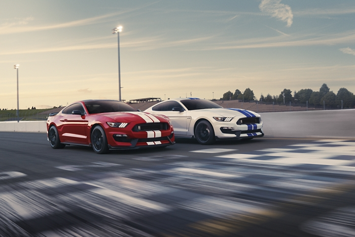 A pair of 2020 Ford Mustang G T three fifties racing on a track