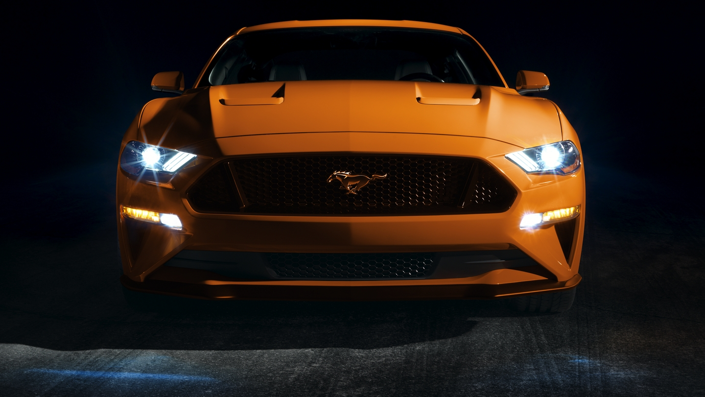 Front view of a 2020 Ford Mustang with L E D front lighting in a dark room