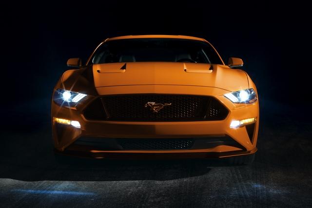 Vista frontal de un Ford Mustang 2020 con las luces L E D delanteras en una habitación oscura