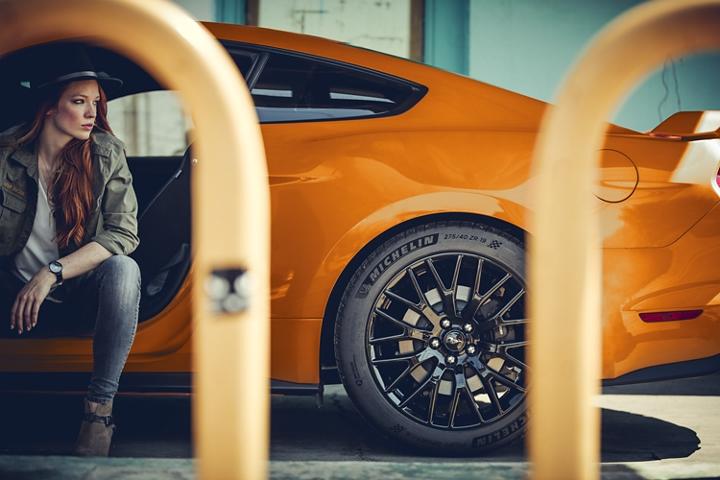 Una mujer sentada en un Ford Mustang G T 2020 en Twister Orange Metallic tinted clearcoat