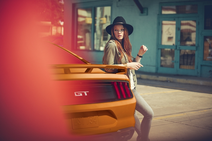 Una mujer con sombrero se asoma a un Ford Mustang G T 2020 en Twister Orange Metallic tinted clearcoat