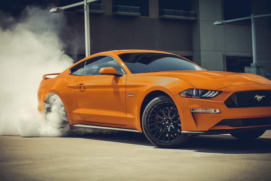 2020 Ford Mustang in twister orange doing a burnout with smoke surrounding the rear tires