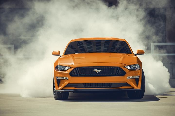 Ford Mustang G T 2020 en Twister Orange Metallic tinted clearcoat recalentado con humo rodeando los neumáticos traseros