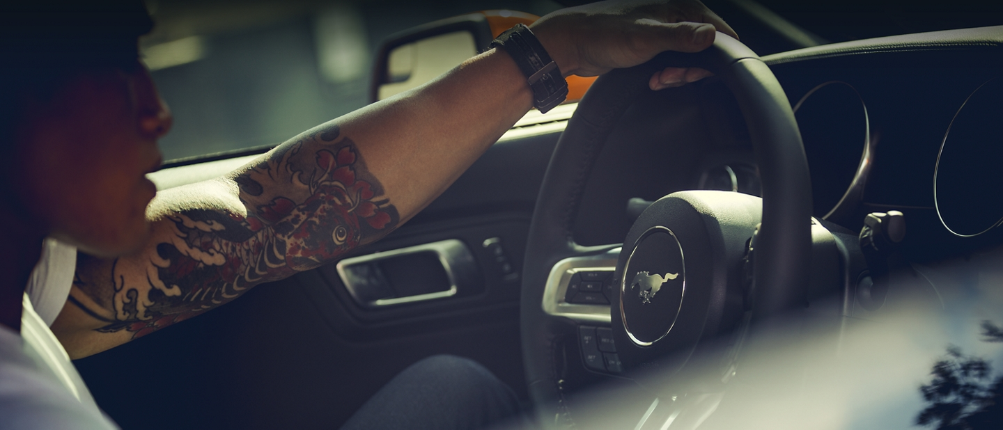 A man with tattoos behind the wheel of a 2020 Ford Mustang