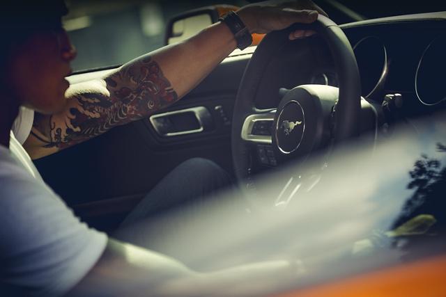 Hombre con tatuajes al volante de un Ford Mustang 2020