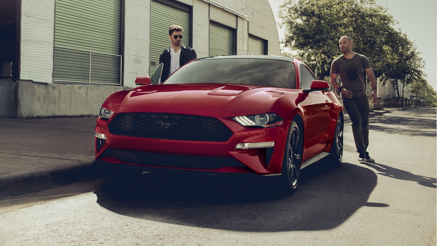 Two people stand near a 2020 Ford Mustang in Rapid Red