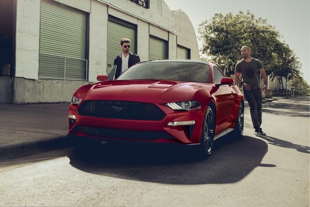 Dos personas de pie cerca de un Ford Mustang 2020 en Rapid Red