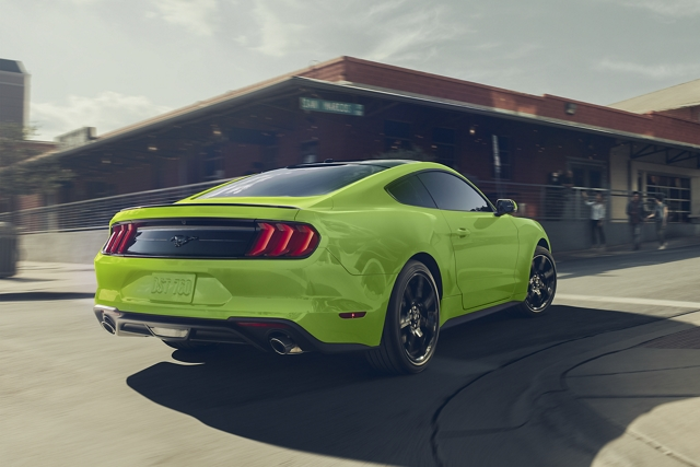 2020 Ford Mustang in grabber lime being driven past a school