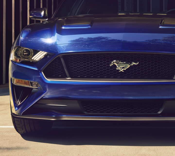 A man and a woman walk away from a 2020 Ford Mustang in kona blue