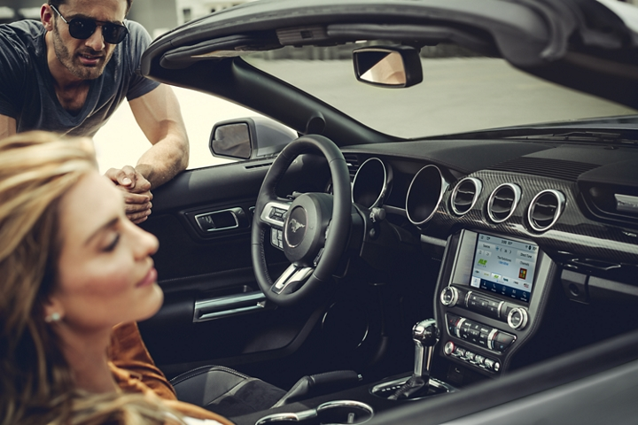 A man talks to a woman seated in a 2020 Ford Mustang featuring the new Carbon Sport Interior Package