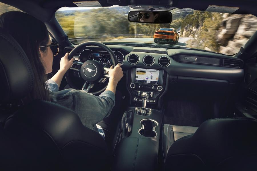 Una mujer en el asiento del conductor de un Ford Mustang 2020 siguiendo a un Ford Mustang 2020 en Twister Orange