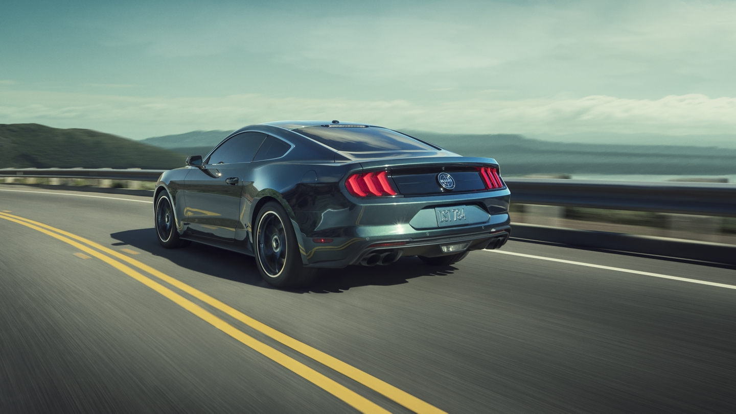 A 2020 Ford Mustang BULLITT going around a curve near the ocean