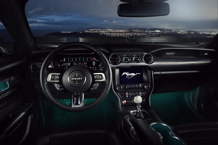Interior del Ford Mustang BULLIT 2020 desde el cual se aprecia una vista nocturna de la ciudad