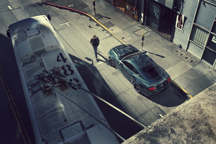 Vista desde arriba de un hombre que se acerca a un Ford Mustang BULLIT 2020