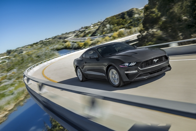 A 2020 Ford Mustang being driven around a curve in the mountains