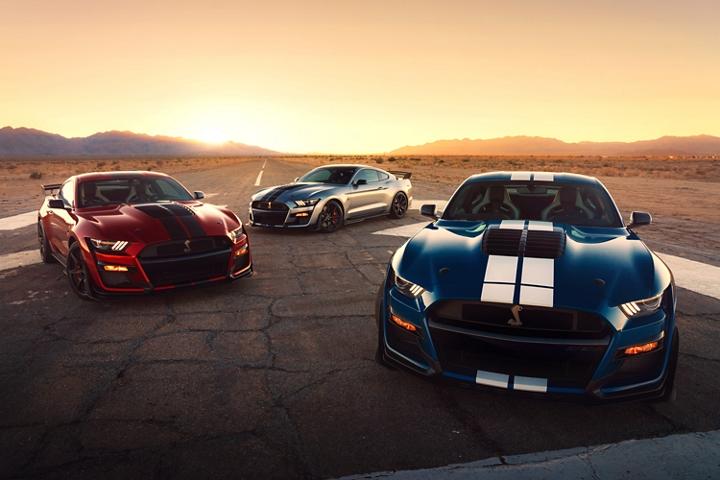 Tres Ford Mustang G T 500s 2020 estacionados en una carretera en el desierto.