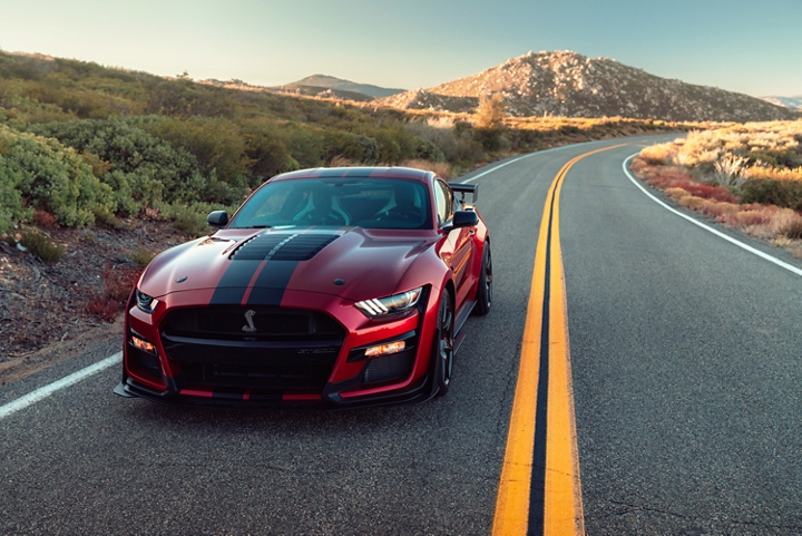 A 2020 Ford Mustang G T 500 in Rapid Red being driven on an empty desert road