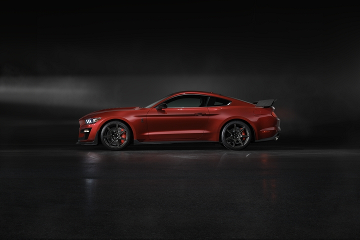 Side view of a 2020 Ford Mustang G T 500 in rapid red in a dark room