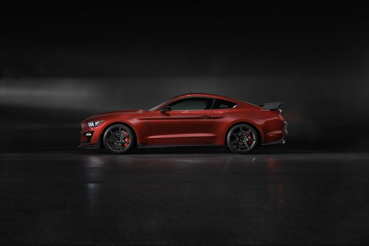 Vista lateral del Ford Mustang G T 500 2020 en Rapid Red en una habitación oscura