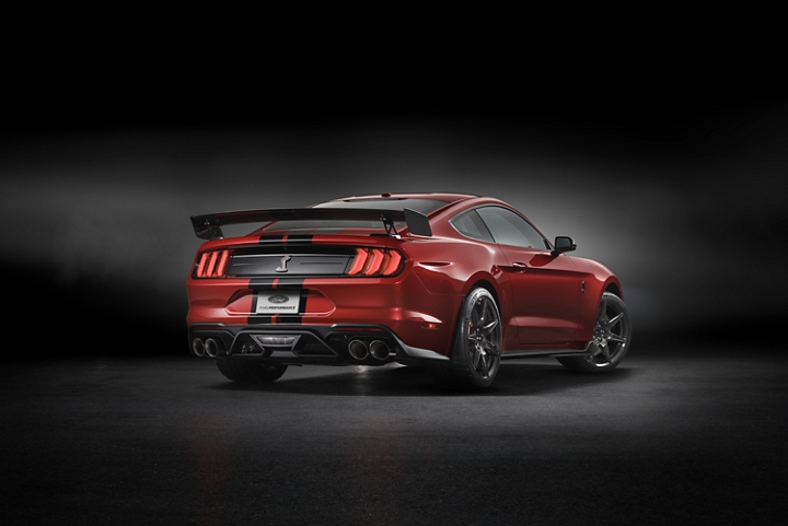 Rear view of a 2020 Ford Mustang G T 500 in rapid red in a dark room
