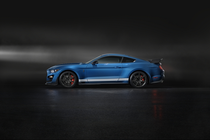 Side view of a 2020 Ford Mustang G T 500 in blue in a dark room