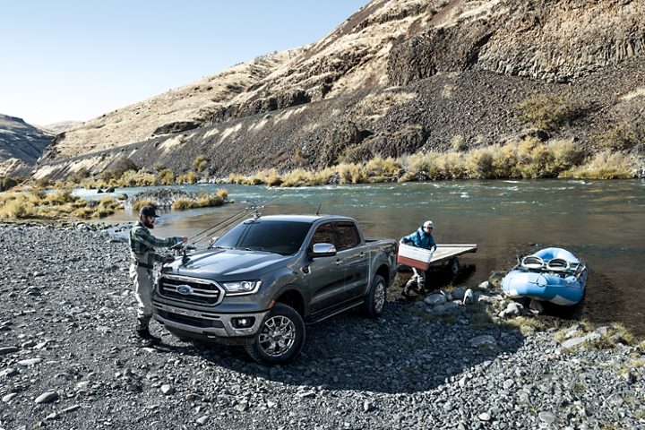 Men at river bank unloading rubber raft from trailer on 2019 Ford Ranger