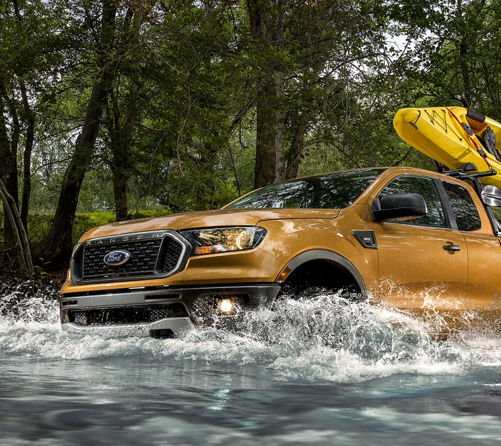 2019 Ford Ranger crossing street with kayak mounted on optional bed rack accessory
