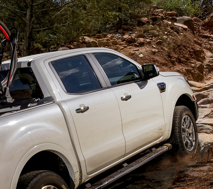 2019 Ford Ranger going up dirt and rock covered path shown with optional bed mounted rack accessory
