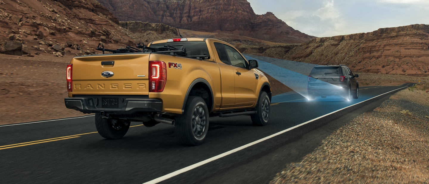 2019 Ford Ranger traveling behind a vehicle on paved road through desert area