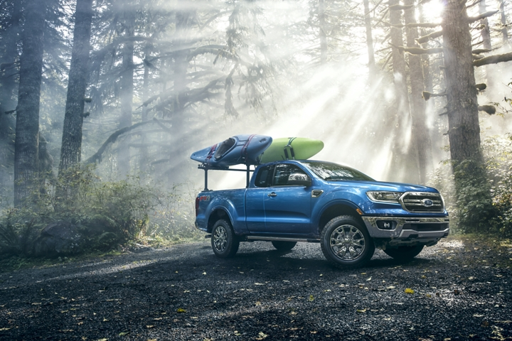 2020 Ford Ranger in Lightning Blue on forest road with kayaks on optional bed mounted rack accessory