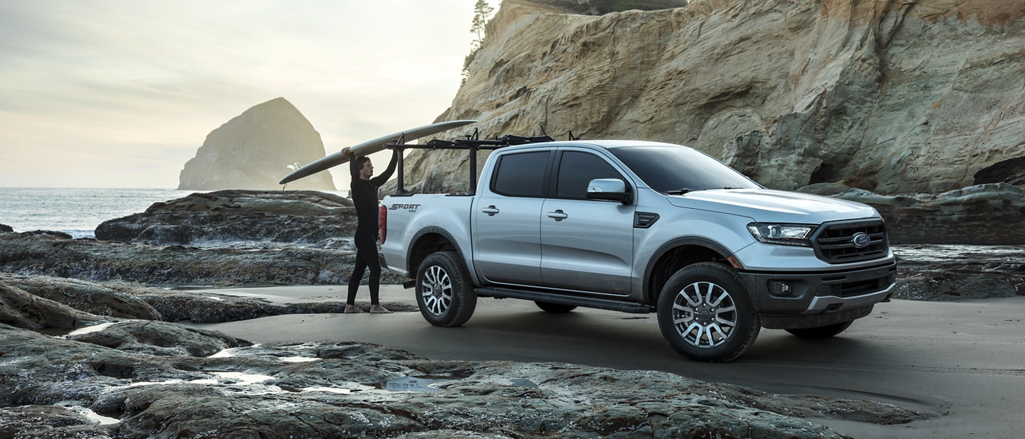 2020 Ford Ranger in Iconic Silver with a man loading a surfboard in the bed