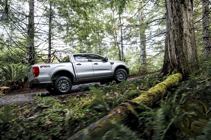 2020 Ford Ranger X L T traveling uphill on forest road with optional bed mounted rack accessory