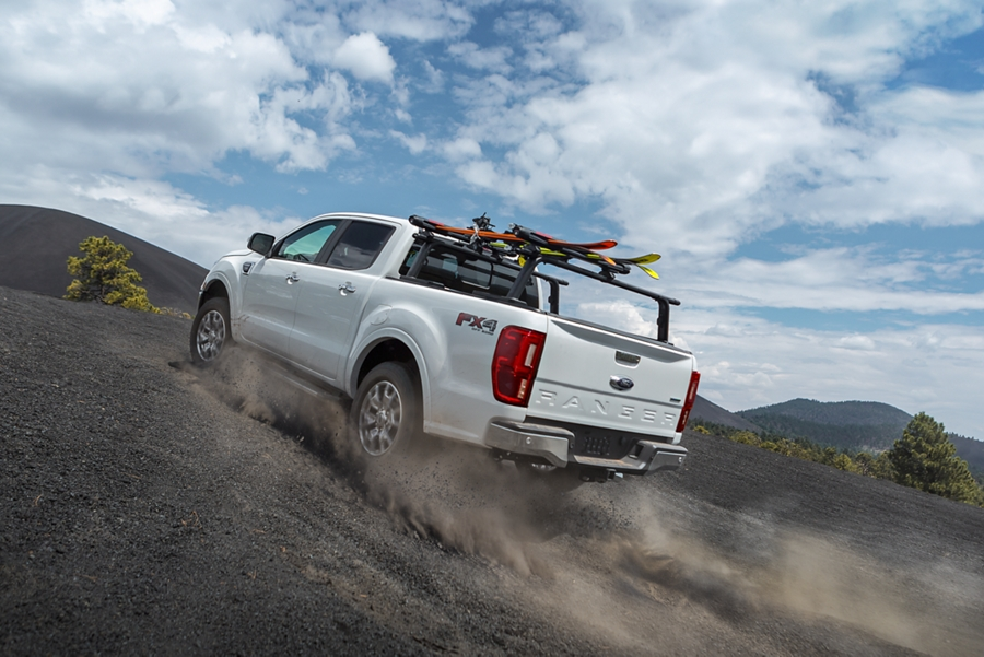 2020 Ford Ranger LARIAT F X 4 shown in Oxford White kicking up dust