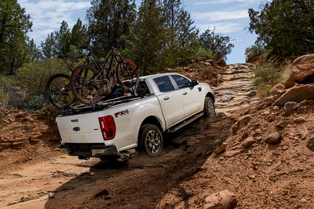 2020 Ford Ranger with F X 4 Off Road Package in Oxford White being driven uphill with trail bikes on bed rack