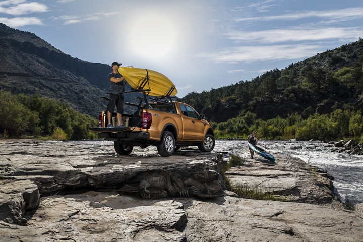 2020 Ford Ranger LARIAT SuperCab in Saber with optional bed mounted rack accessory shown with man loading a kayak