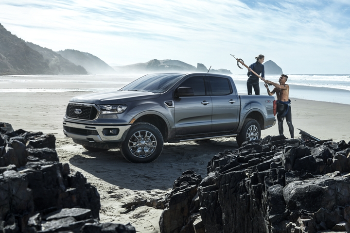 2020 Ford Ranger at rocky ocean beach with two men getting ready to hit the surf