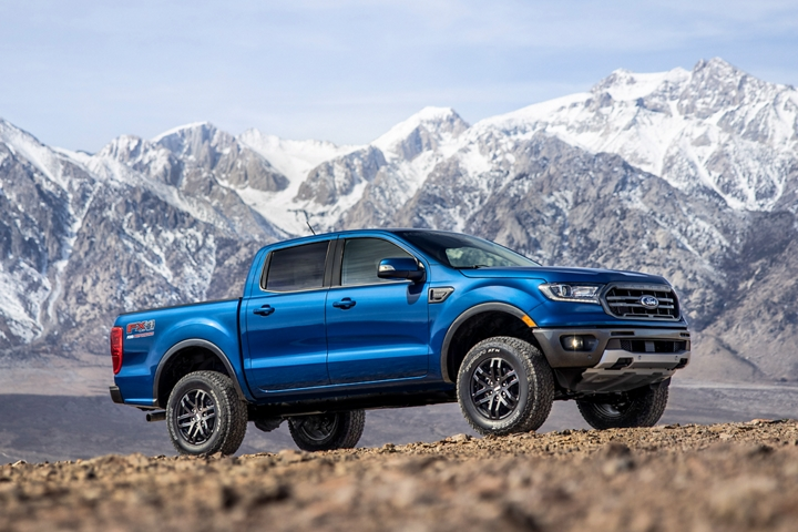 Una Ford Ranger 2020 con Paquete de Desempeño Ford Nivel1 enLightning Blue estacionada en un camino de tierra con montañas de fondo