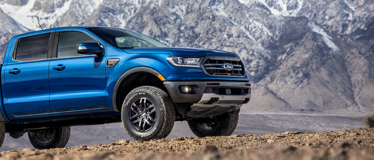 2020 Ford Ranger with Ford Performance Level 1 Package in Lightning Blue parked on dirt with mountains in background