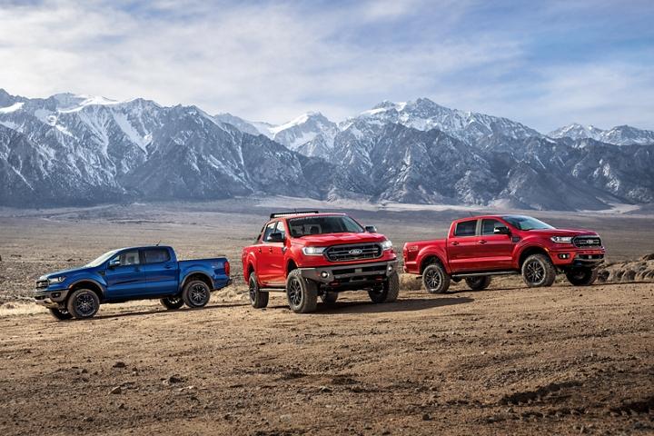 Varios modelos de Ford Ranger 2020conPaquetes de DesempeñoFord estacionados en la tierra enfrente de unpaisajemontañoso