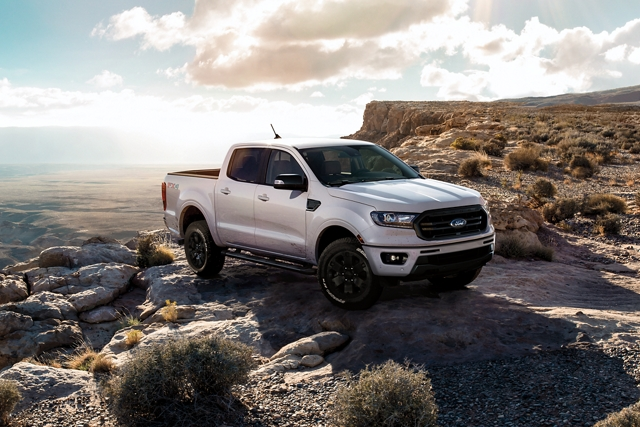 2020 Ford Ranger with black grille with black surround and 18 inch black painted wheels on a mountain