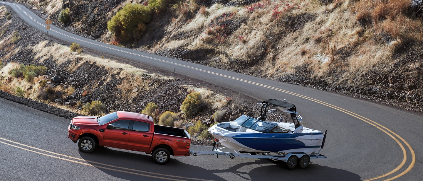 2020 Ford Ranger in Rapid Red Metallic Tinted Clearcoat towing a boat on remote winding two lane paved road