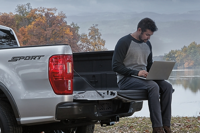 Young man with laptop sitting on the open tailgate of 2020 Ford Ranger