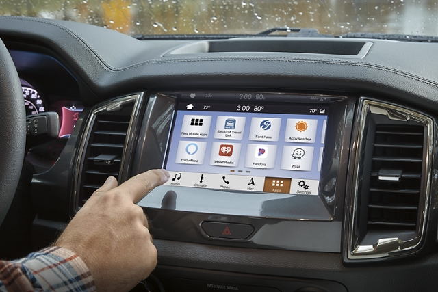 Hand selecting a music button on the screen of the 2020 Ford Ranger