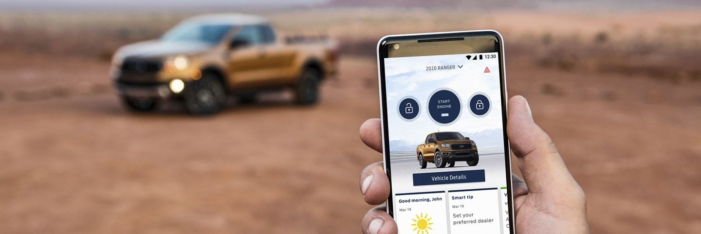 A hand holds a smartphone displaying a 2020 Ford Ranger in Saber Orange pickup in the FordPass App