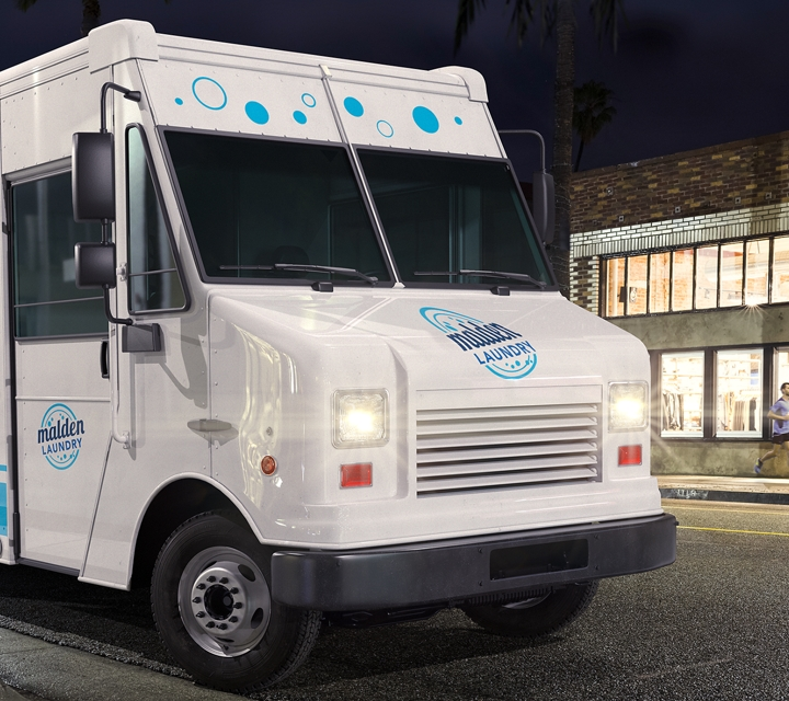 Commercial laundry service vehicle being driven at night
