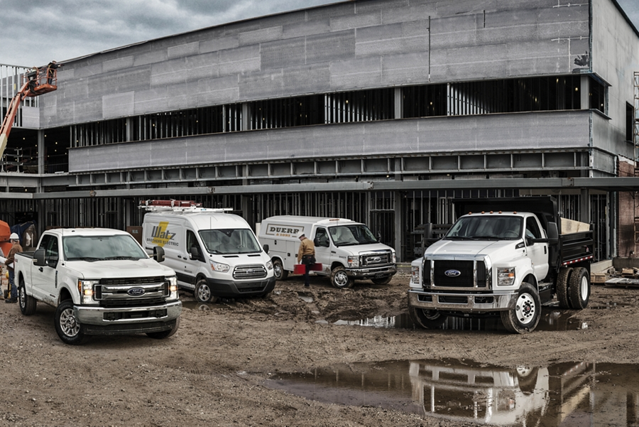 Ford Super Duty Transit Cargo Van E Series Cutaway and Medium Duty trucks with aftermarket equipment at construction site