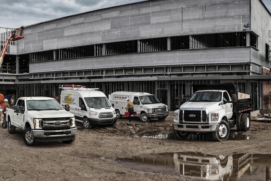 Las camionetasFord Super Duty Transit Cargo Van E Series Cutaway y para Trabajo Mediano con equipo no original en un sitio de construcción