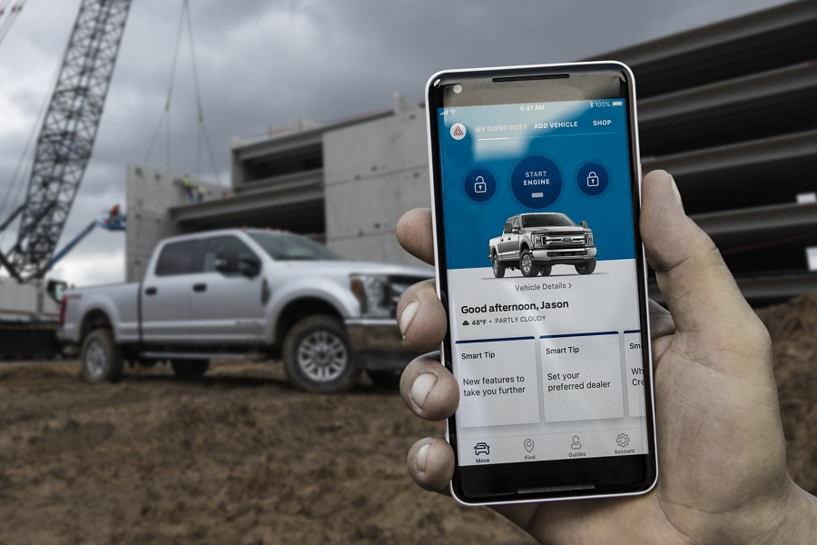 Person at worksite holding their smartphone displaying Ford Pass app