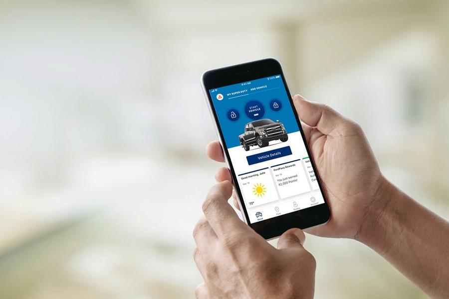 Una mano sosteniendo un teléfono con la aplicaciónFordPass activada